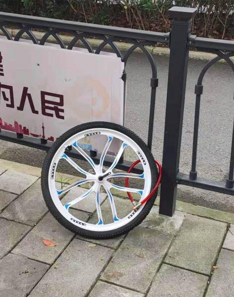 新闻有故事:人行道护栏上锁着一只孤零零的车轮